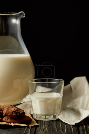 partial view of fresh milk in jug and glass, chocolate cookies and sackcloth on black background