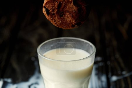 closeup view of chocolate cookie falling into glass with milk