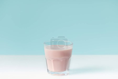 closeup view of strawberry milkshake in glass on blue background