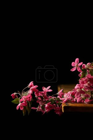 close-up shot of aromatic pink cherry flowers lying on wooden tabletop