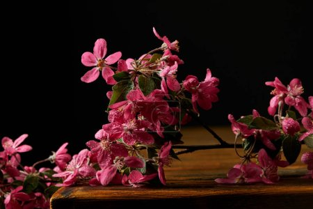 close-up shot of aromatic pink cherry blossom lying on wooden tabletop