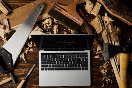 laptop with blank screen surrounded by axe, handsaw, chisel, paintbrush and hammer on wooden table