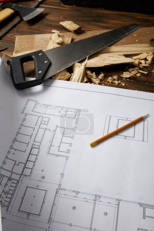 Photo for Closeup view of architectural blueprint, pencil, handsaw, axe and coping saw on wooden table - Royalty Free Image