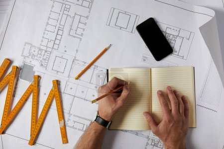 cropped image of architect writing in blank textbook on blueprint with pencil, smartphone and collapsible meter