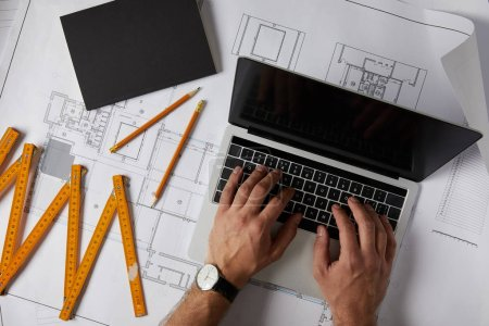 Photo for Cropped shot of architect with laptop, collapsible meter, pencils and textbook on blueprint - Royalty Free Image