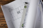 elevated view of spirit level on blueprint at wooden table