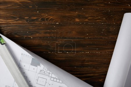 top view of spirit level and blueprint on wooden brown table
