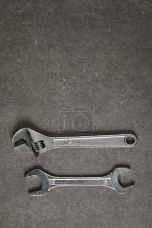 top view of adjustable wrench and spanner on gray surface