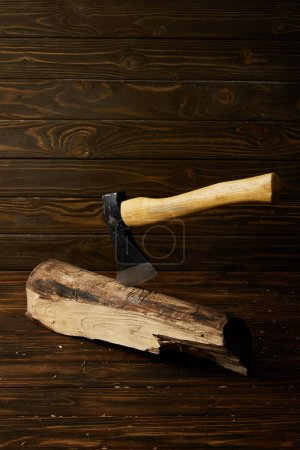 close up shot of sticking axe in log on brown wooden surface