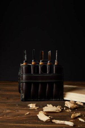 Photo for Closeup shot of chisels in leather case and wooden pieces on table - Royalty Free Image