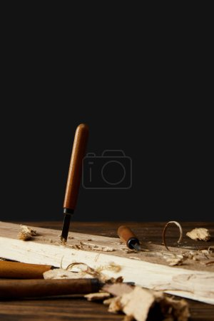 sticking chisel in wood at table on black background