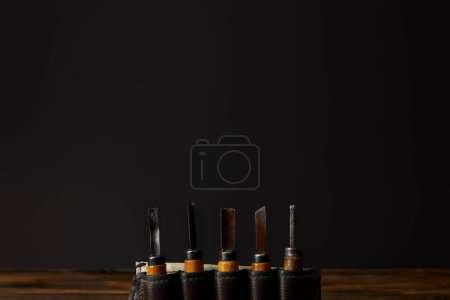 chisels in leather case at table on black background