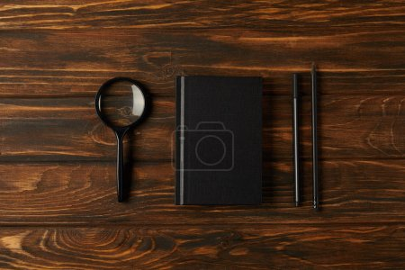 top view of magnifying glass, notebook and office supplies on wooden table
