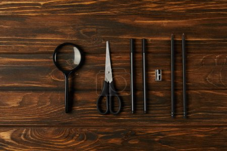 top view of magnifying glass, scissors and office supplies on wooden table