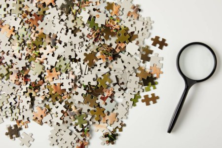 top view of magnifying glass and jigsaw puzzle pieces on grey