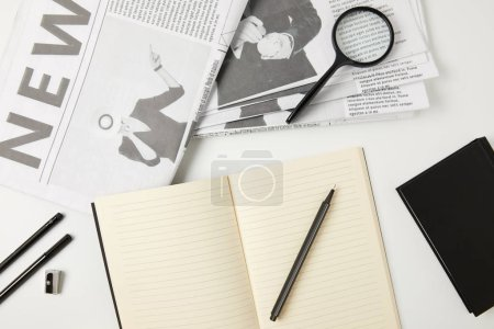 top view of notebooks, newspapers, office supplies and magnifying glass on grey