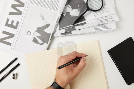 partial top view of person writing in blank notebook, newspapers, magnifying glass, notebook and office supplies on grey