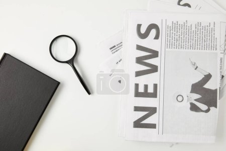 top view of notebook, magnifying glass and newspapers isolated on grey
