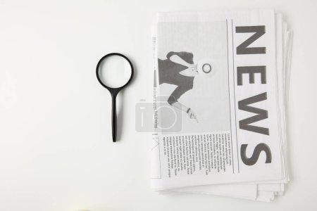 top view of magnifying glass and newspapers isolated on grey