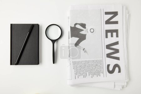 top view of notebook with pen, magnifying glass and newspapers isolated on grey