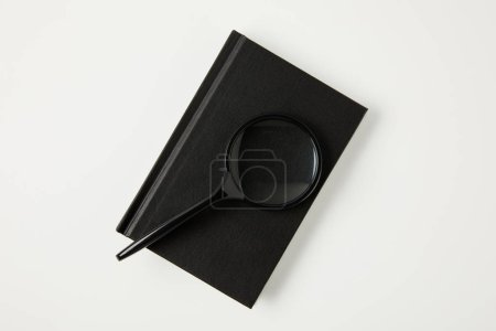 top view of magnifying glass on black notebook isolated on white