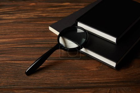 close-up view of magnifying glass and black books on wooden table