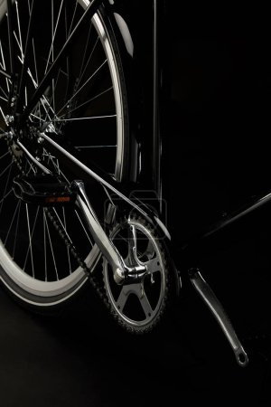 close-up view of pedals, chain and wheel of classic bicycle isolated on black