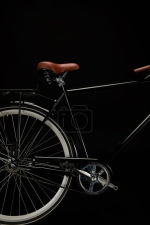 wheel, saddle and pedals of classic bicycle isolated on black