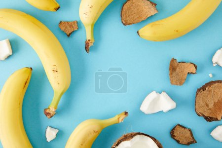 top view of arranged coconut pieces and bananas isolated on blue
