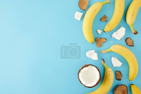 Photo for Top view of arranged coconut pieces and bananas isolated on blue - Royalty Free Image