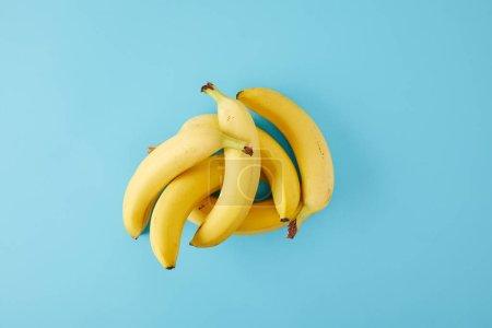 Foto de Vista superior de plátanos frescos dispuestas aisladas en azul - Imagen libre de derechos