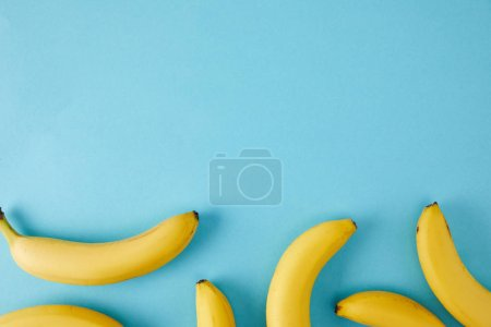 Photo for Top view of arranged fresh bananas isolated on blue - Royalty Free Image