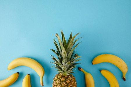 flat lay with fresh bananas and pineapple isolated on blue