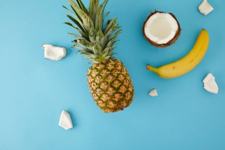 Photo for Flat lay with ripe pineapple, banana and coconut pieces isolated on blue - Royalty Free Image