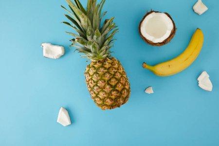 Foto de Endecha plana con maduros pedazos de piña, plátano y coco aislado en azul - Imagen libre de derechos