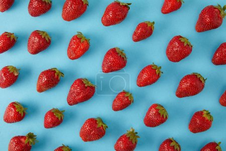 full frame of arranged fresh strawberries isolated on blue