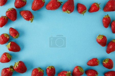 top view of arranged fresh strawberries isolated on blue