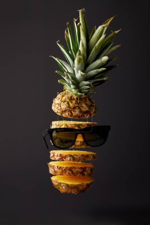 close up view of cut ripe pineapple and sunglasses isolated on black