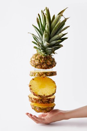 partial view of female hand and fresh cut pineapple isolated on white