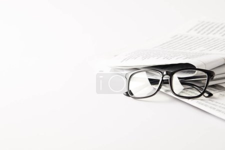 pile of newspapers with eyeglasses, on white background with copy space