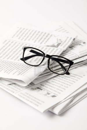 close up of pile of newspapers and eyesight, on white