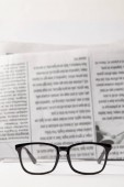selective focus of black eyewear and newspaper on background, black and white