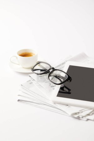 eyeglasses and digital tablet on pile of newspapers and coffee cup, on white
