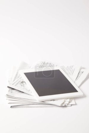 digital tablet with blank screen on pile of newspapers, on white