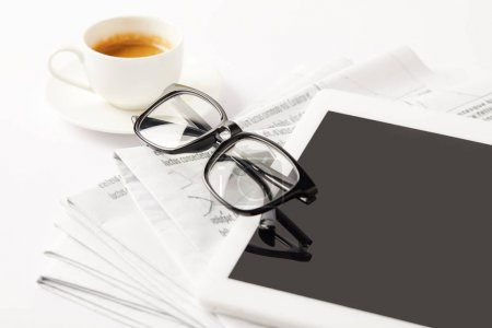 Photo for Eyeglasses, coffee cup, digital tablet and pile of newspapers, on white - Royalty Free Image