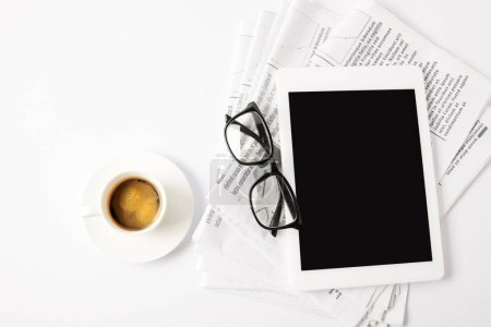 top view of glasses, cup of coffee, digital tablet and pile of newspapers, on white