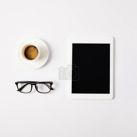 flat lay with cup of coffee, eyeglasses and digital tablet with blank screen, on white