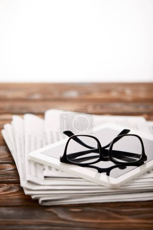 eyeglasses, digital tablet and pile of newspapers, on wooden background