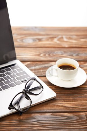 laptop, eyeglasses and coffee cup on wooden surface