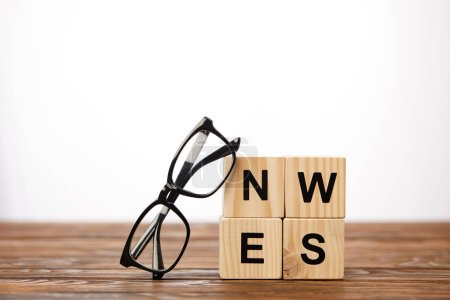 Photo for Eyeglasses and alphabet cubes making word news on wooden surface, on white background - Royalty Free Image